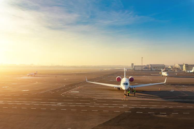 Flugzeug am Flughafen mit Sonnenuntergang im Hintergrund
