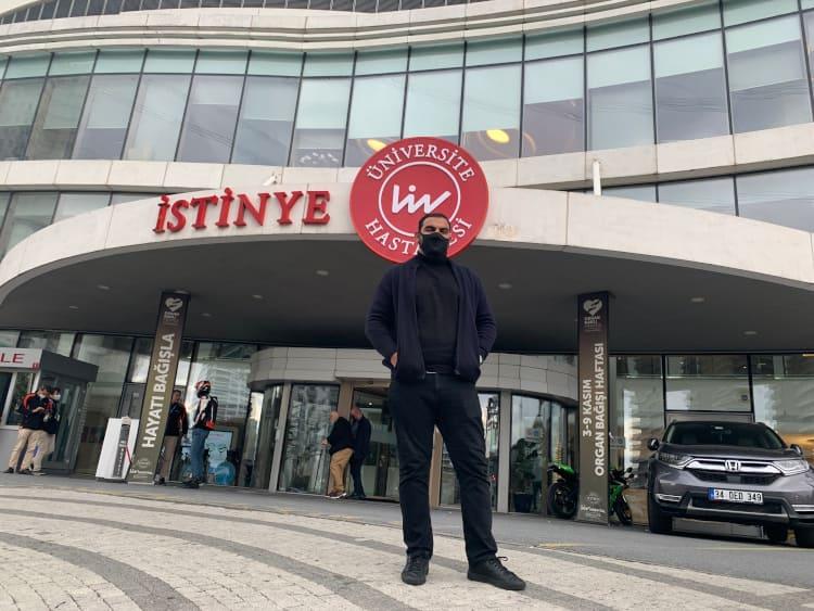 Mann steht vor der Klinik für die Haartransplantation in der Türkei während Corona