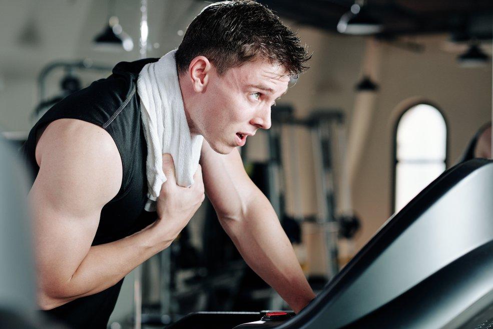 Hombre sudoroso en gimnasio: el sudor excesivo es una causa de tiña del cuero cabelludo