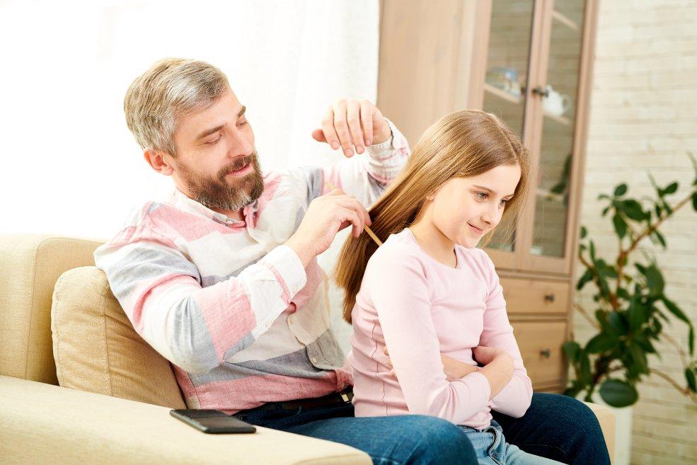 Padre peinando a su hija: el contagio de tiña de la cabeza puede darse entre dos personas