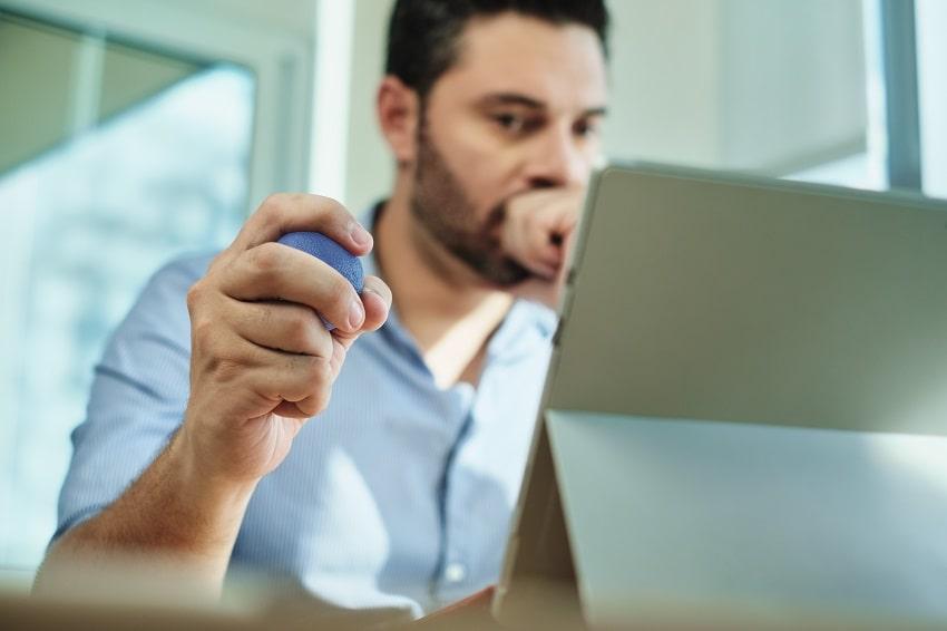 Uomo al computer usa una pallina anti-stress