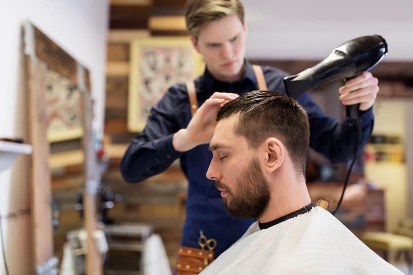 Parrucchiere asciuga i capelli prima dell'acconciatura