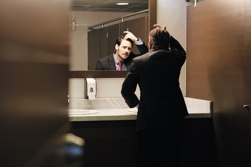 Uomo sotto stress per la perdita di capelli si guarda allo specchio