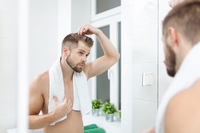 Uomo preoccupato per caduta capelli da piastra e trattamenti cosmetici