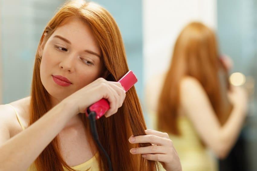 Ragazza usa la piastra preoccupata per la caduta dei capelli