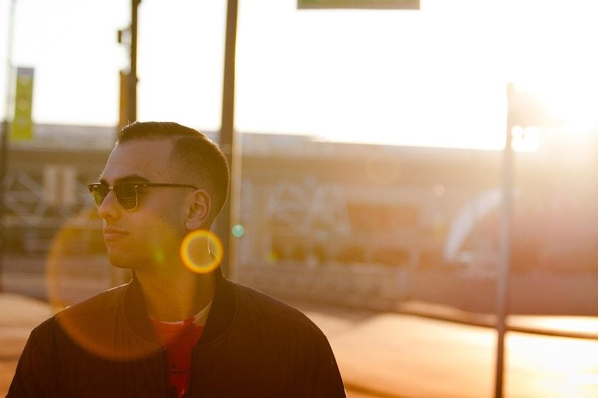Mann mit Sonnenbrille steht in der Sonne