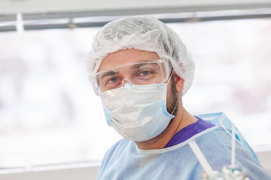 Arzt mit Mund- und Augenschutz