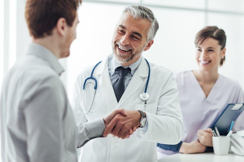 Arzt schüttelt die Hand eines Patienten, da keine Pickel nach der Haartransplantation entstanden sind