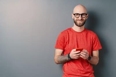attraktiver glatzer Mann mit Brille und roten T-Shirt