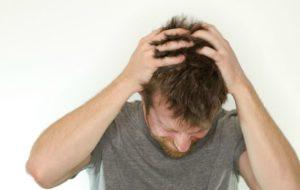Juckende Kopfhaut nach Haartransplantation - Junge Mann juckt seinen Kopf