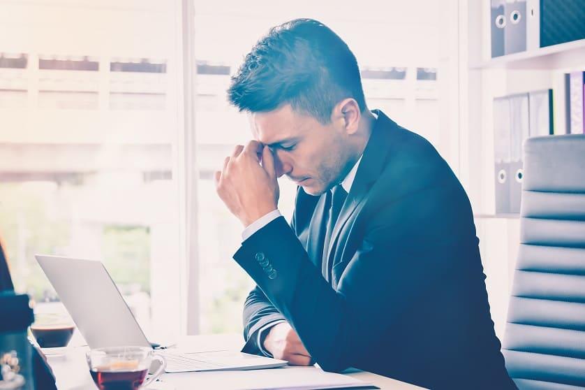 Mann sitzt gestresst bei der Arbeit vor dem Laptop