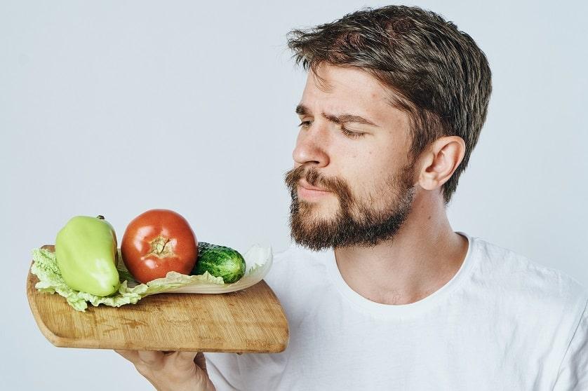 Mann überlegt welches Essen gegen Haarausfall geeignet ist
