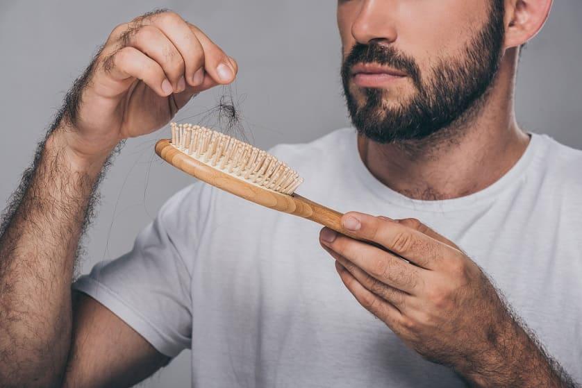 Mann zieht Haare aus der Bürste