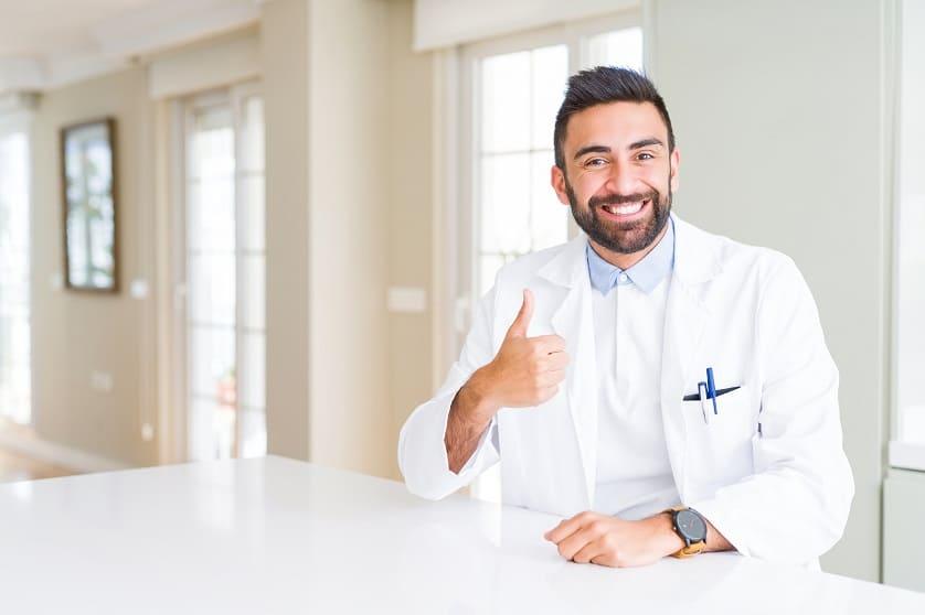 Lächelnder Arzt hält Daumen hoch