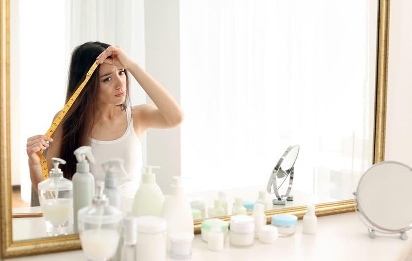 Frau vor dem Spiegel beim Nachmessen von Haarausfall