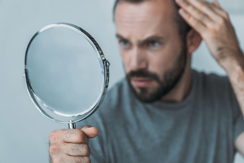 Mann schaut unzufrieden in den Spiegel