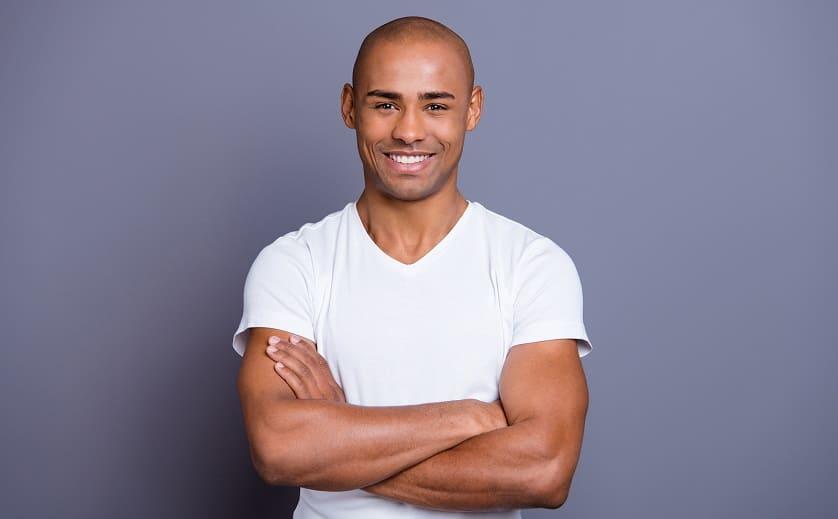 Selbstbewusster Mann mit Glatze lächelt