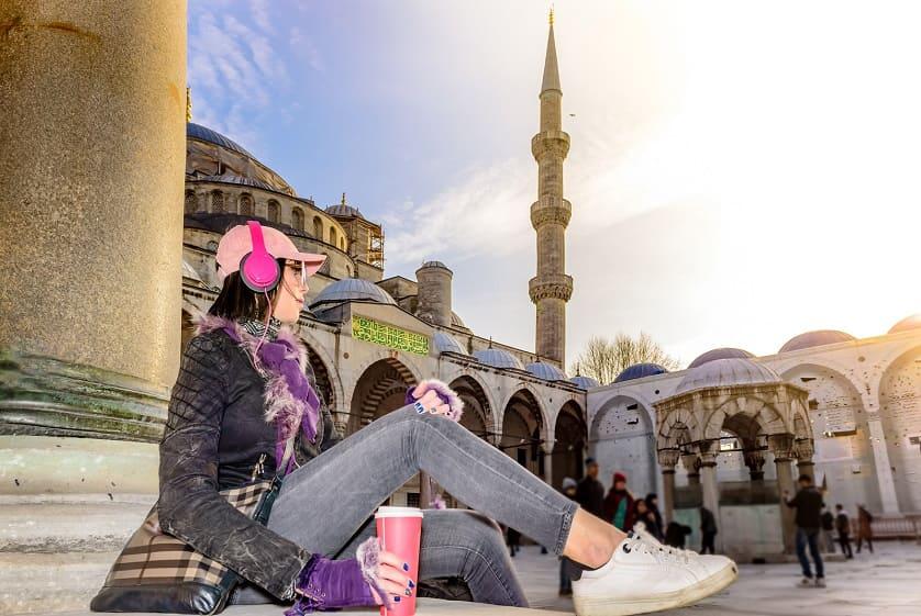 Junge Frau mit Kaffee und Kopfhoerern sitzend vor der blauen Moschee in Istanbul