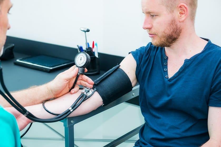 Der Arzt führt eine Blutdruckmessung bei seinem Patienten durch
