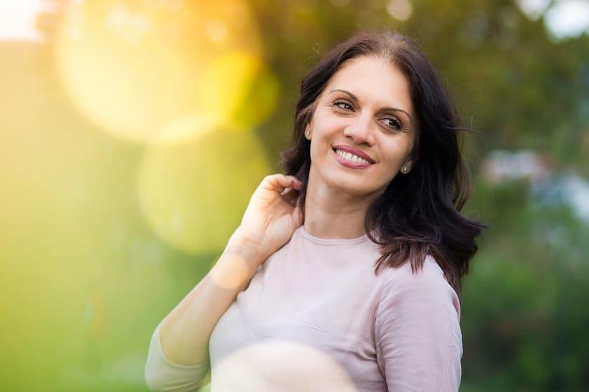 Frau in den Wechseljahren steht lächelnd in der Natur