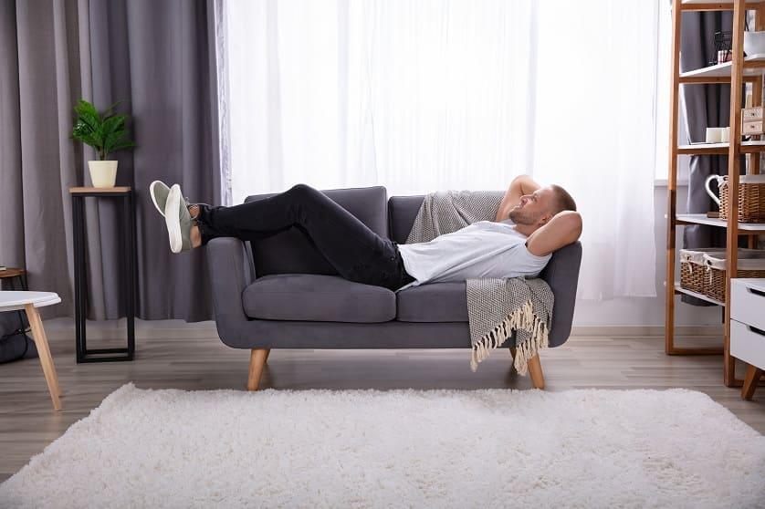 Mann entspannt auf dem Sofa