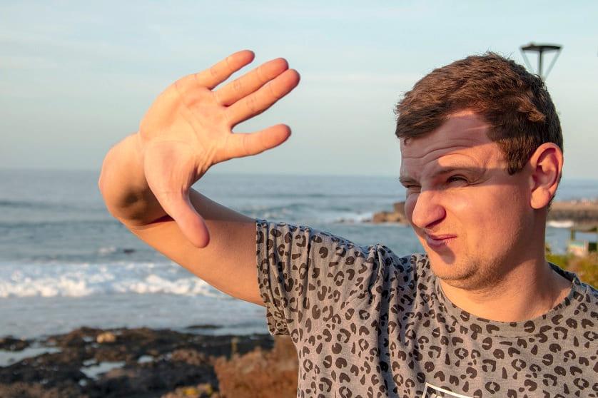 Mann hält die Hand vors Gesicht