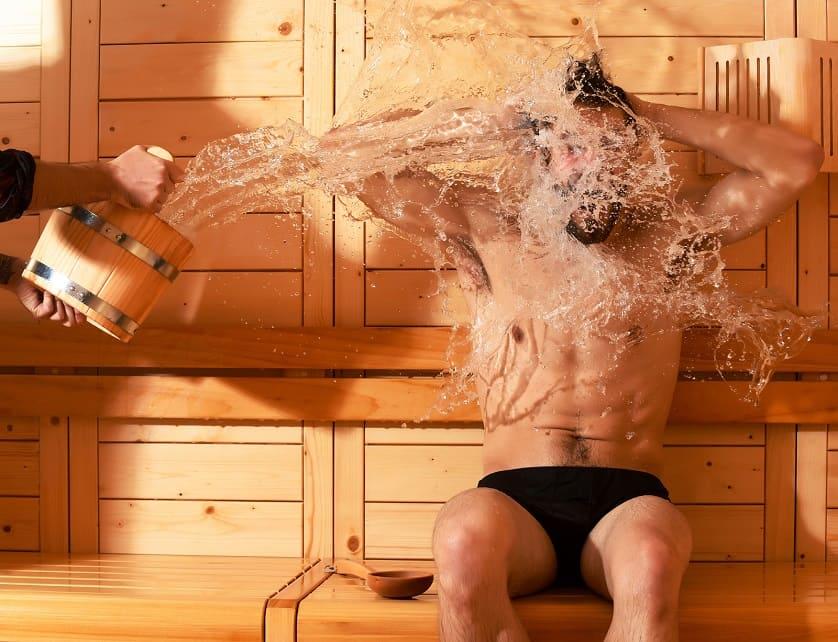 Mann in der Sauna bekommt Wasser ins Gesicht