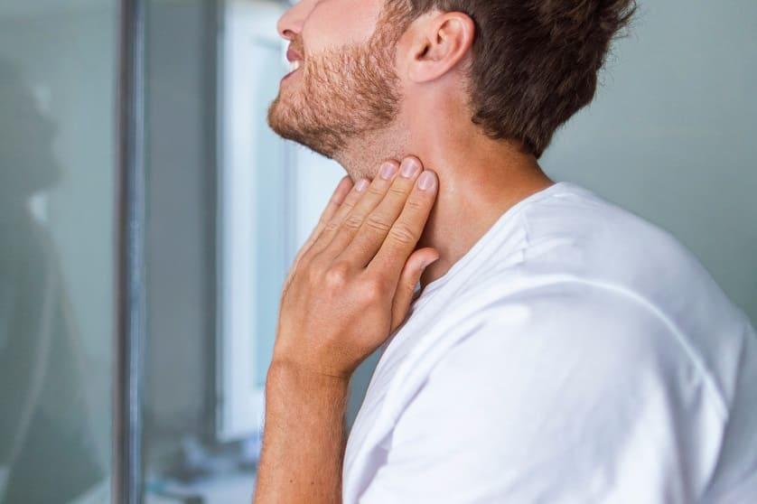 Mann fässt sich an den Hals