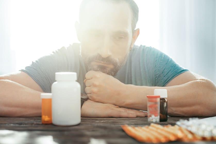 Mann hängt über dem Tisch und überlegt welches Medikament er nehmen soll