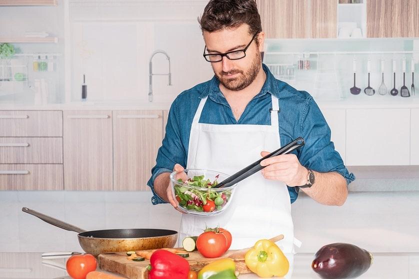 Veganer bereitet sich sein Essen in der Küche zu