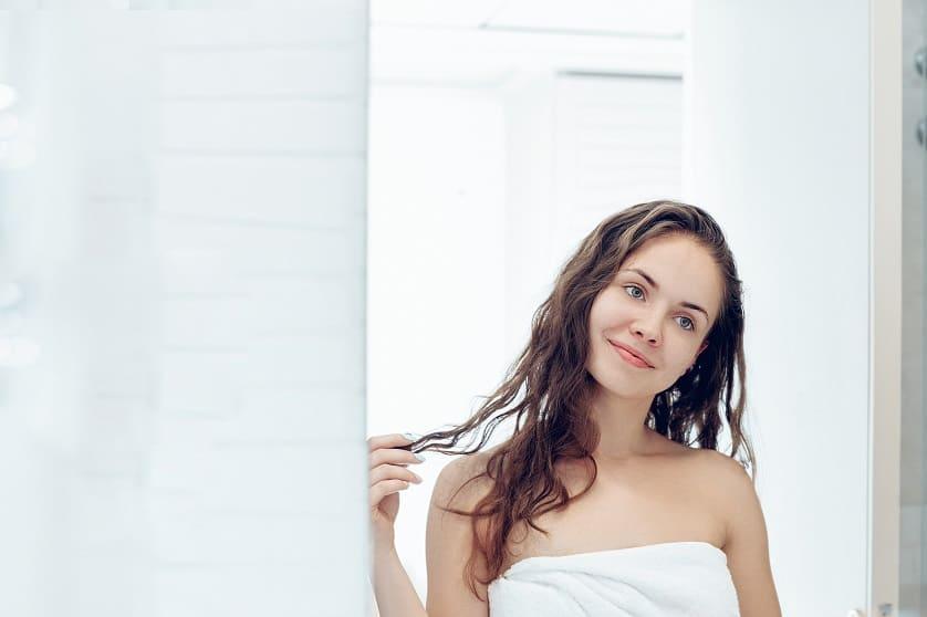 Frau hat Conditioner in den Haaren und steht lächelnd vor dem Spiegel