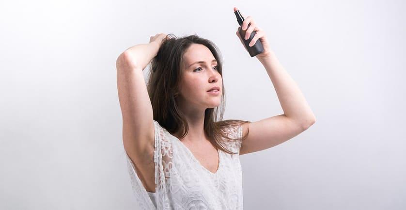 Frau benutzt wasserabweisendes Haarspray gegen elektrische Haare