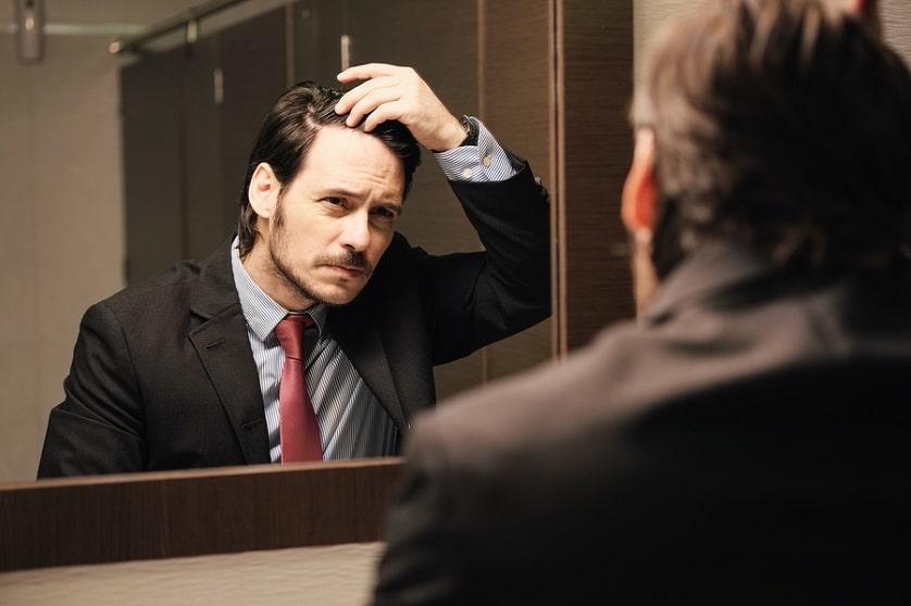 Mann schaut in den Spiegel und tastet seine Haarlinie ab