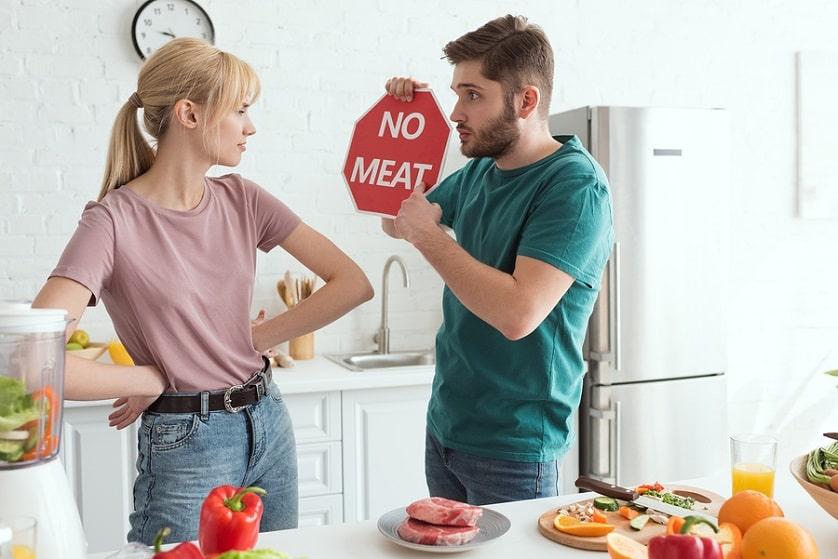 Mann hält neben seiner Frau ein Schild in der Hand wo drauf steht dass man kein Fleisch essen soll