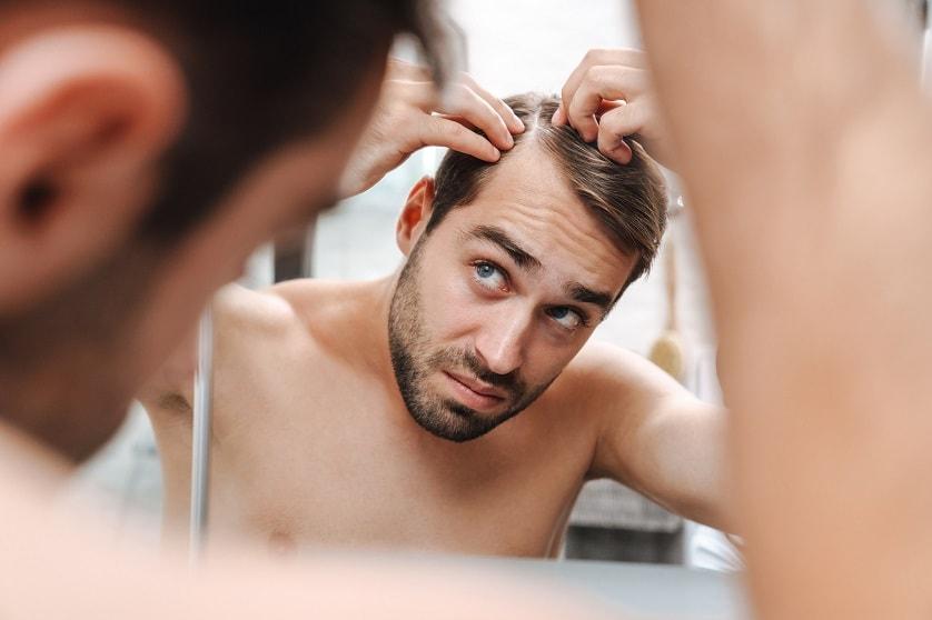 Mann steht vor dem Spiegel und schaut sich seine Geheimratsecken an