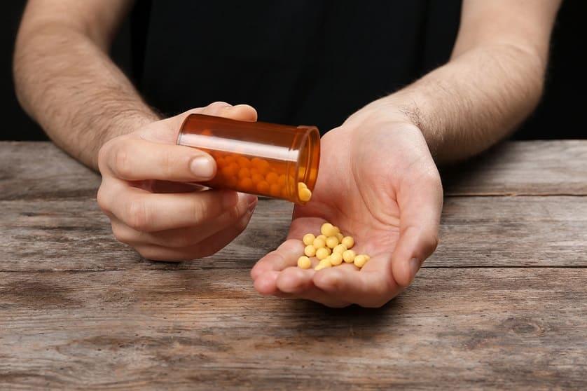 Mann schüttet gelbe Pillen in die Hand