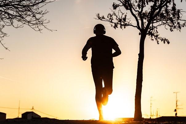 Mann joggt bei Sonnenuntergang