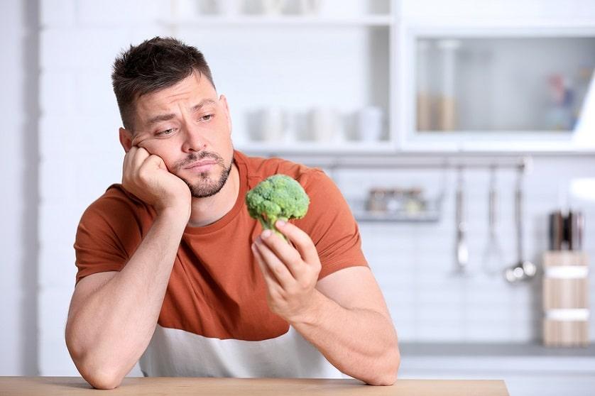 Mann hält ein Stück Brokkoli in der Hand während er darüber nachdenkt ob die vegane Ernährung seine Haare ausfallen lässt