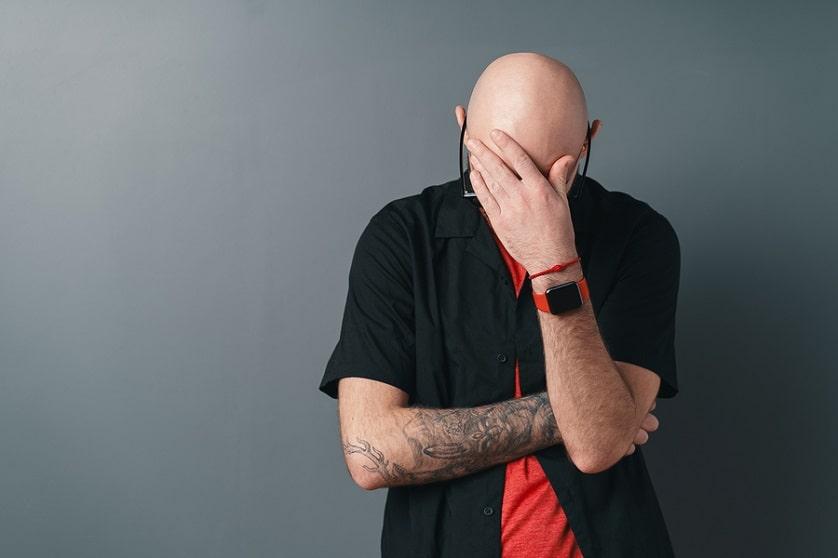 Mann mit Glatze überdeckt sein Gesicht und schaut nach unten