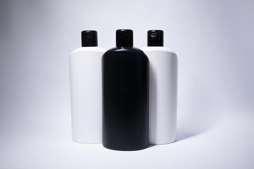 Zwei weiße und eine schwarze Shampooflasche auf weißem Untergrund