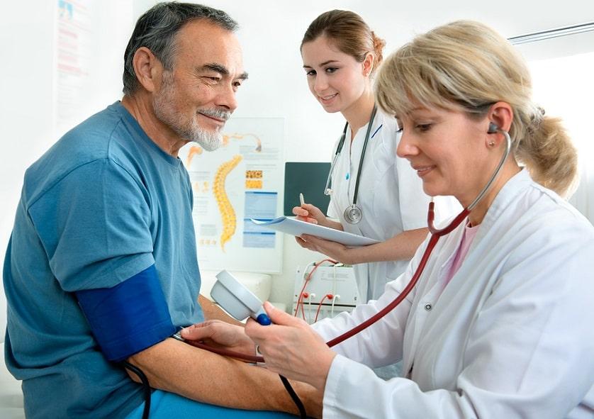 Ärztin misst den Blutdruck eines Patienten