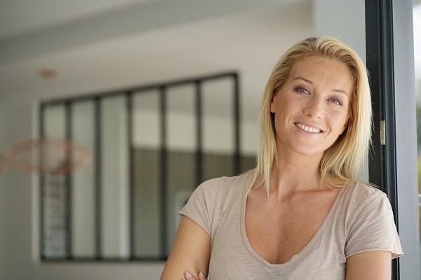 Blonde Frau grinst in die Kamera