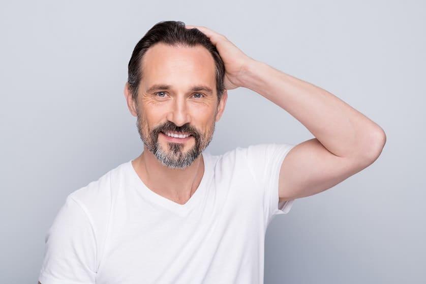 Mann mit Haarausfall fässt sich an den Hinterkopf