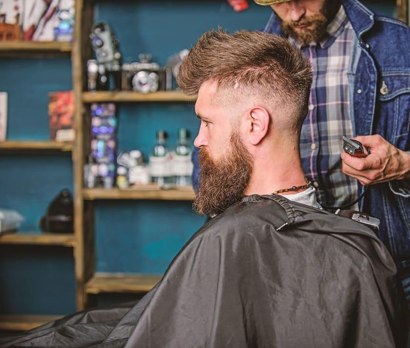 Ein Mann sitzt beim Barbier und lässt sich die Haare schneiden