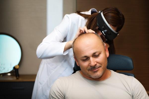 Ärztin untersucht Spenderbereich eines Mannes vor der Haartransplantation.