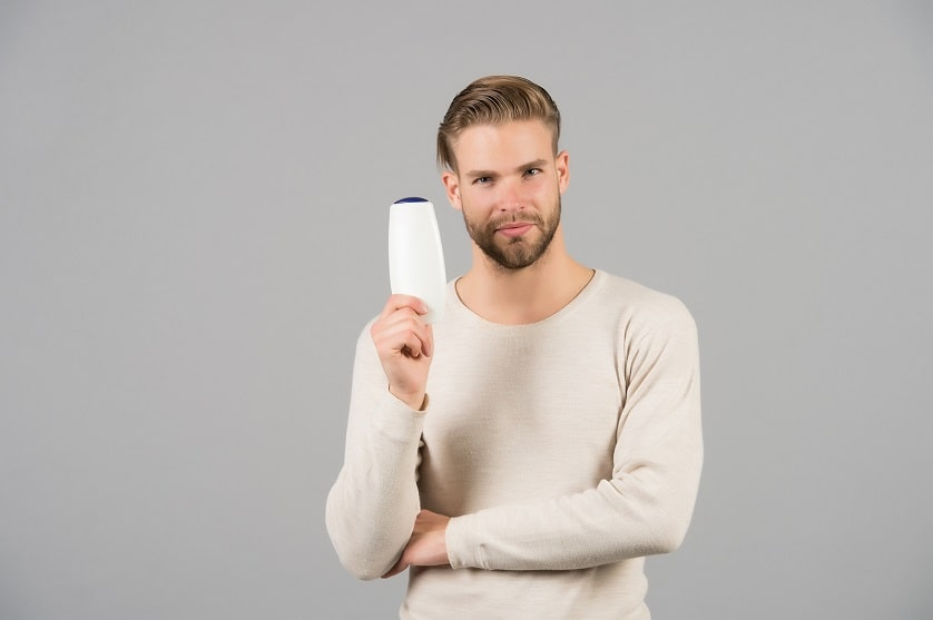 Mann hält ein Anti-Schuppen-Shampoo in der Hand