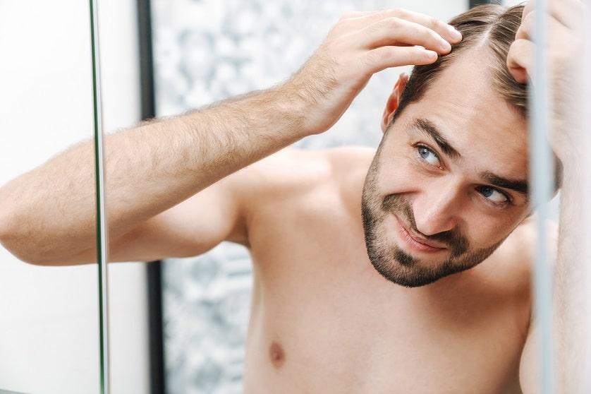 Junger Mann begutachtet seinen Haarausfall im Spiegel seines Badezimmers