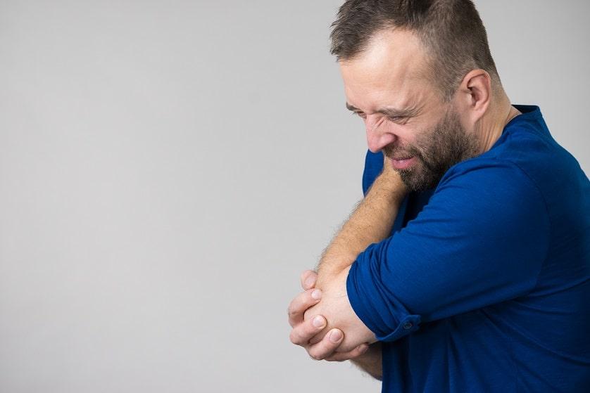 Mann mit Haarausfall und Rheuma hält seinen linken Arm mit einem schmerzverzerrtem Gesicht