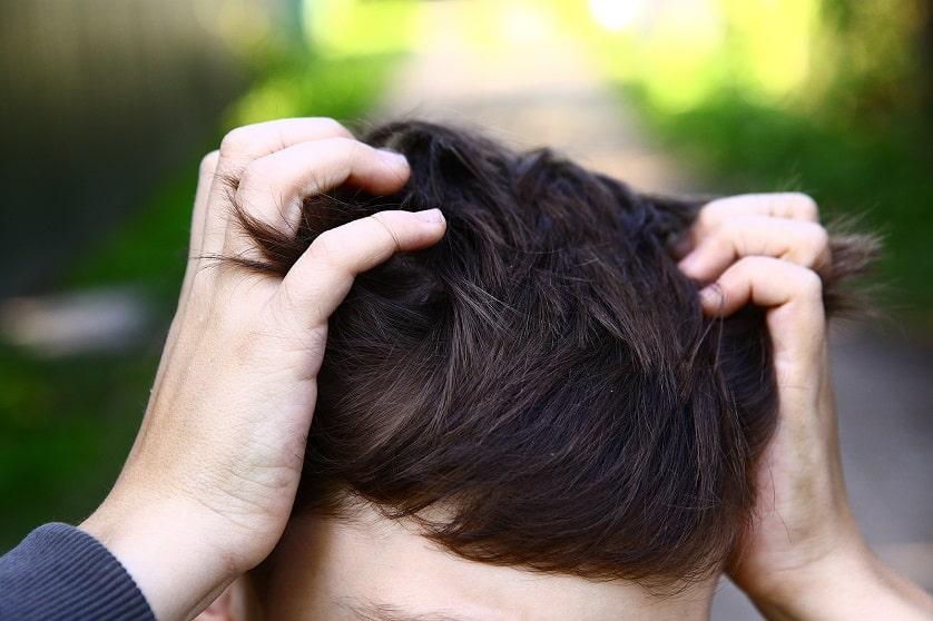 Mann kratzt seinen Kopf