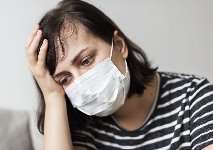 Frau mit Mundschutz leidet an Coronavirus Symptomen